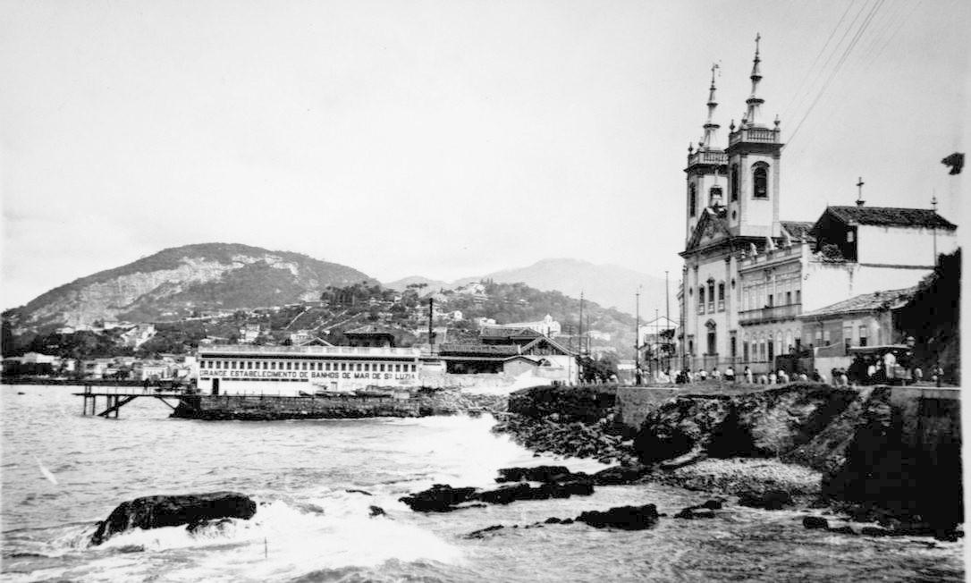 A Casa de Banhos de Mar de Santa Luzia, na época em que o mar chegava até a porta da Igreja de Santa Luzia. O local era um balneário popular para os cariocas no começo do século XX Reprodução/Acervo de Fernando da França Leite