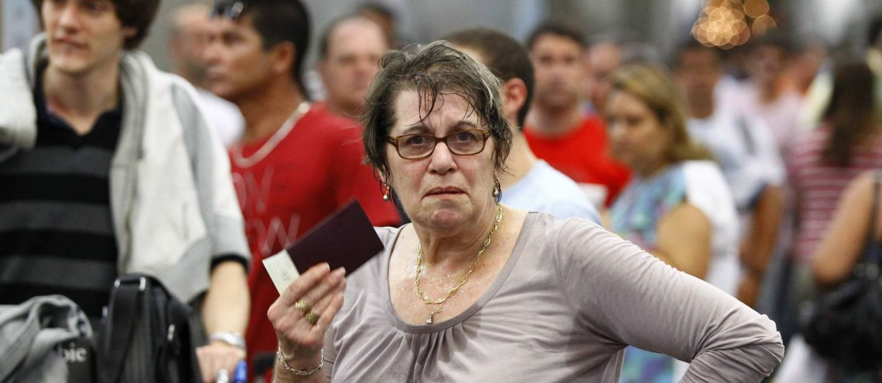 Com muito calor, passageira se abana com o passaporte em fila no Tom Jobim, horas após apagão no aeroporto Foto: Pablo Jacob / O Globo