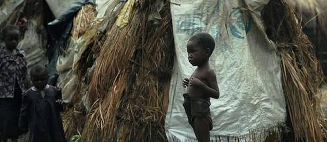 Um menino congolês desabrigado aguarda do lado de fora da barraca de sua família durante uma distribuição de comida realizada por organizações humanitárias, em Mugunga Foto: TONY KARUMBA / AFP