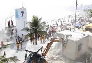 Operários da prefeitura derrubam cabine da Polícia Militar que estava sendo construída irregularmente no calçadão do Arpoador Foto: Marcelo Carnaval / O Globo