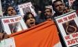"""Manifestantes gritam frases de ordem e agitam cartazes com o texto """"enforquem o estuprador"""" durante um protesto em Nova Délhi, neste sábado (29)"""