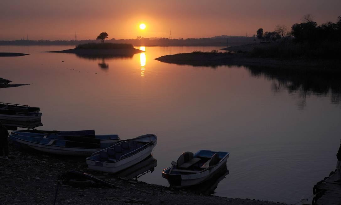 Um paquistanês espera por turistas próximo a seu barco no último pôr-do-sol de 2012, em um lago em Islamabad AAMIR QURESHI / AFP