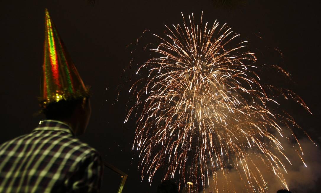 Homem assiste à queima de fogos em celebração de Ano Novo na cidade de Petaling Jaya, na Malásia Lai Seng Sin / AP Photo