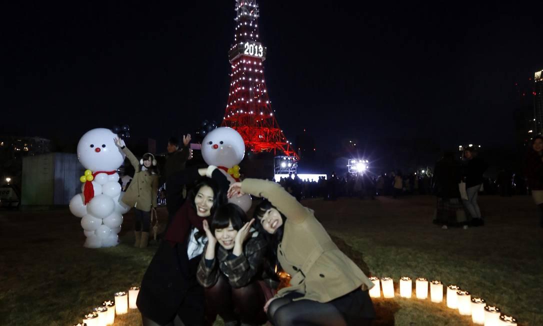 Um grupo de meninas tira fotos em frente à Torre de Tóquio, que recebe uma iluminação especial para celebrar a chegada do Ano Novo Kim Kyung-Hoon / KAZUHIRO NOGI