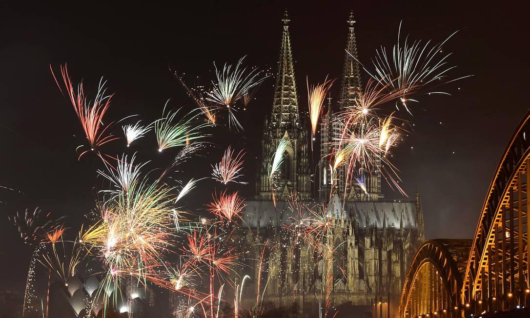 Fogos explodem sobre a igreja Dom, perto do rio Rhine, em Colônia, na Alemanha Patrik Sollarz / AFP