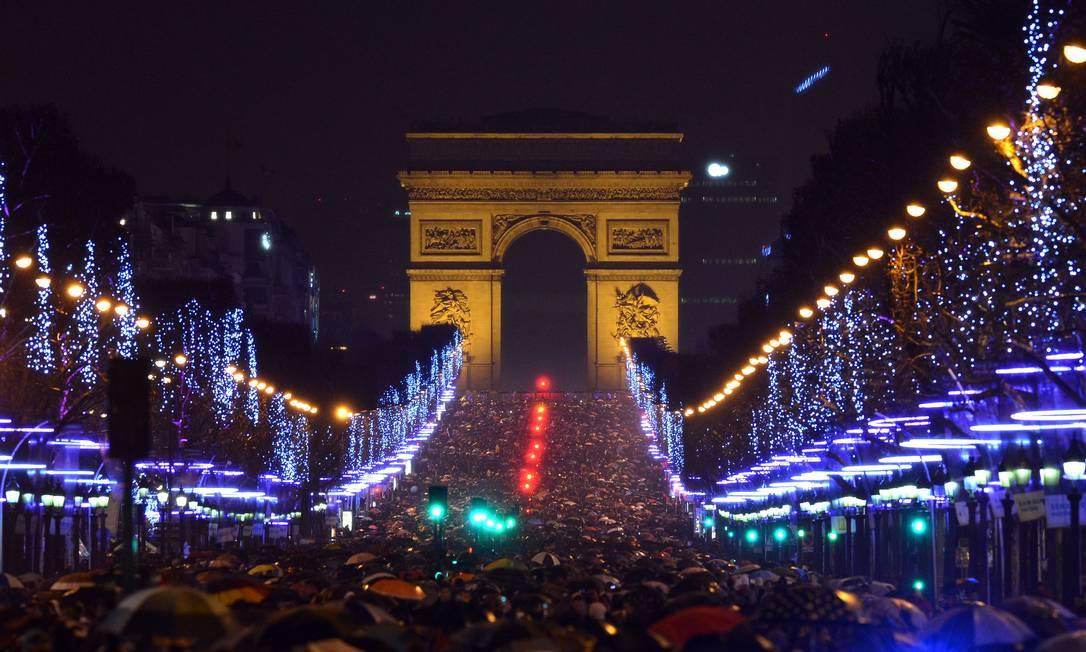 Uma multidão se reúne na Avenida Champs-Elysees em Paris para comemorar o Ano Novo Patrik Stollarz / AFP