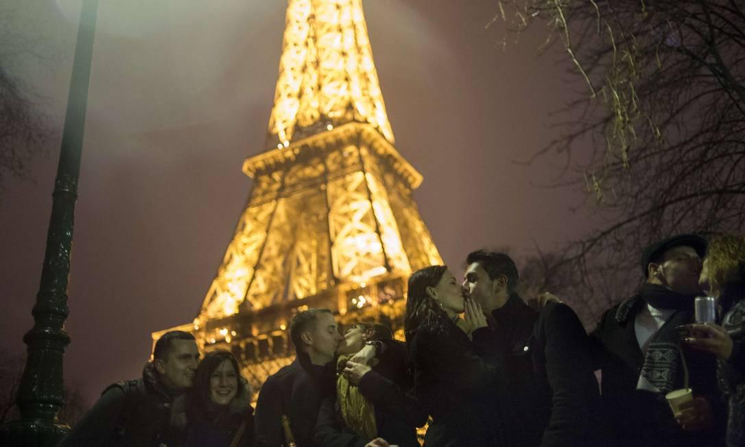 Casais trocam beijos na Praça Trocadero, ao lado da Torre Eiffel, em Paris Fred Dufour / AFP