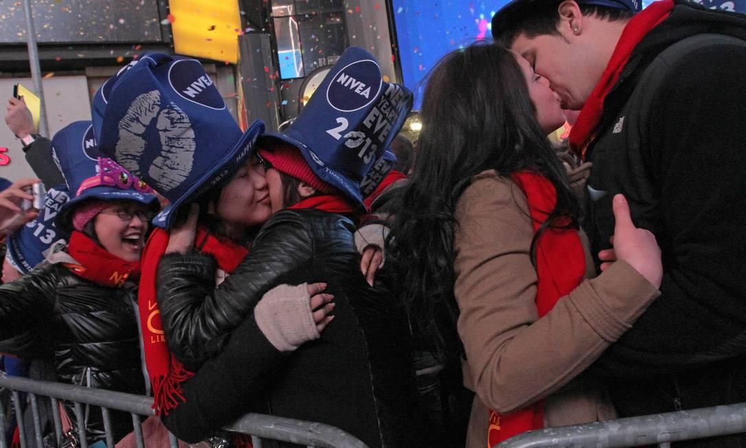 Um casal de namorados se beija, enquanto mãe e filha se abraçam no réveillon da Times Square Tina Fineberg / AP