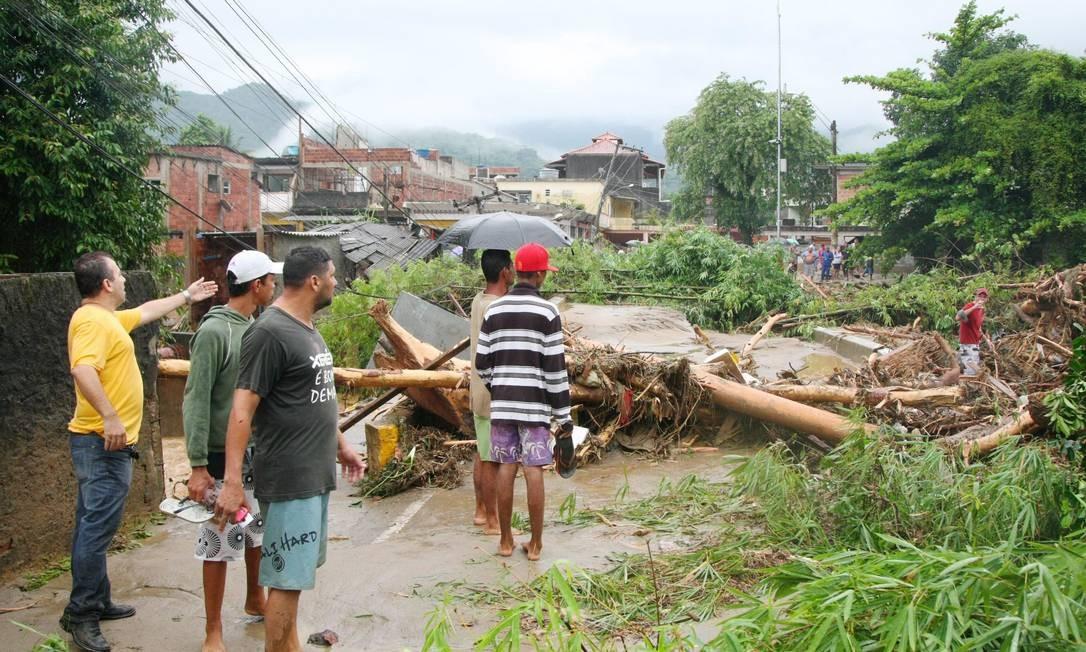 Moradores olham ponte destruída na localidade de Mantiqueira Foto: Fernando Quevedo / O Globo