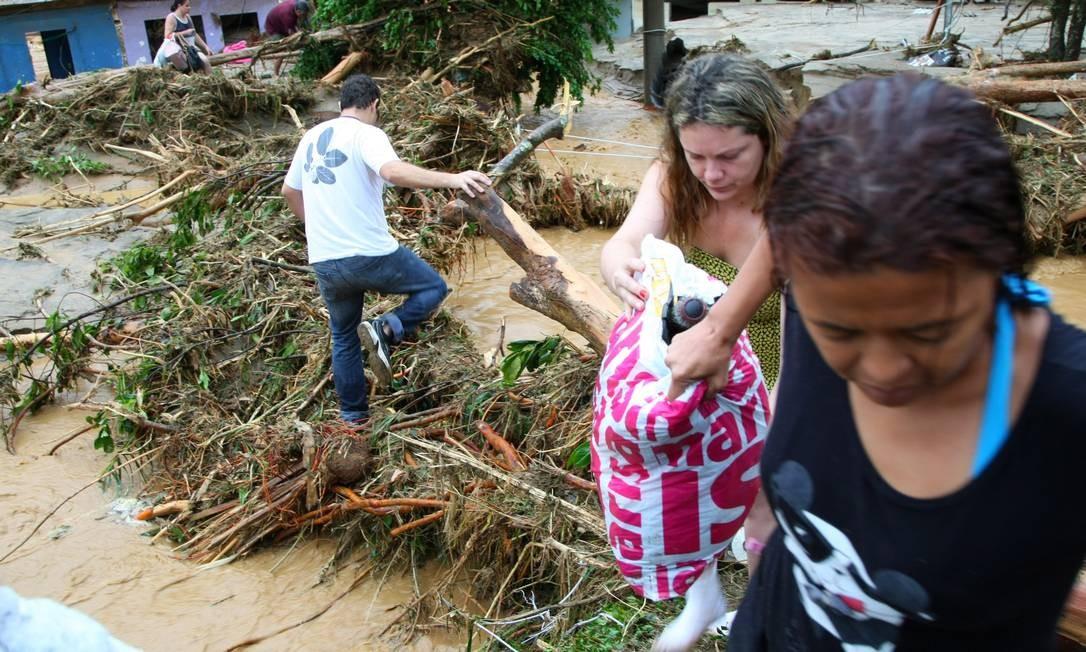 Moradores retiram pertences das casas inundadas em Xerém Foto: Fernando Quevedo / O Globo