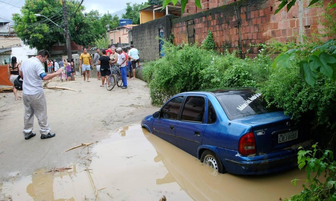 Carro arrastado pela tromba d'água para em rua que foi destruída pelas chuvas. Local está coberto de lama Foto: Fernando Quevedo / O Globo