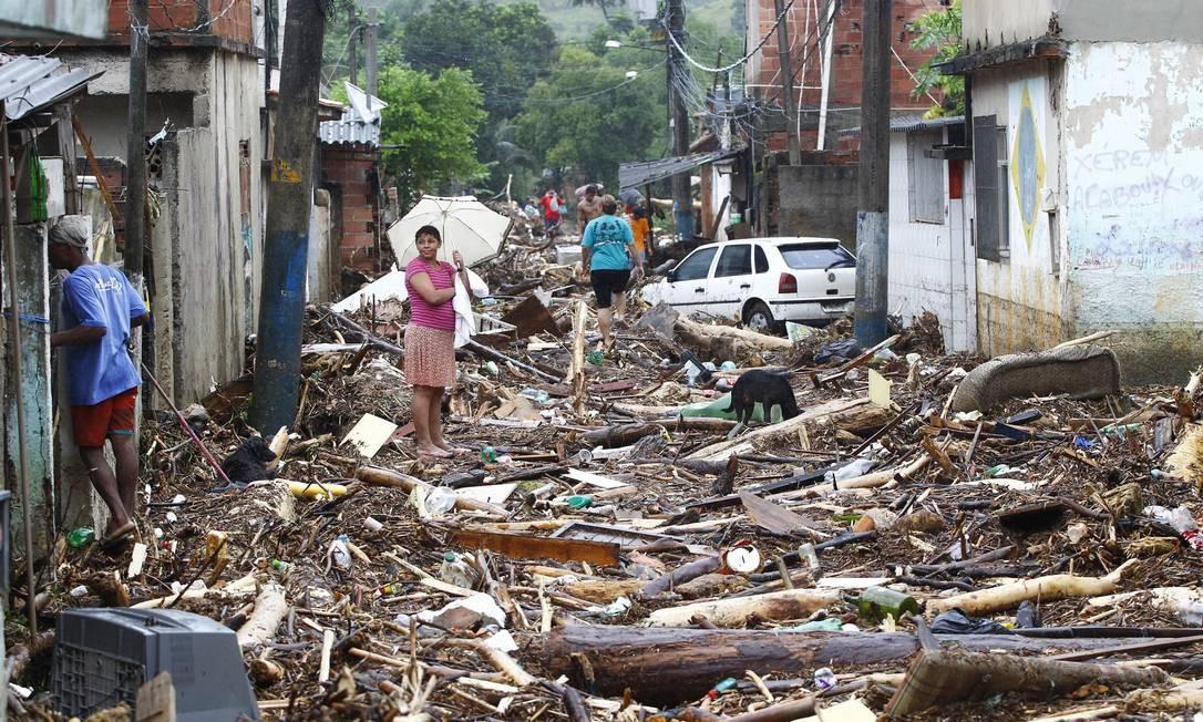 Escombros tomam conta de rua do bairro Café Torrado, em Xerem, depois do transbordamento do rio que corta a região Foto: Pablo Jacob / Agência O Globo