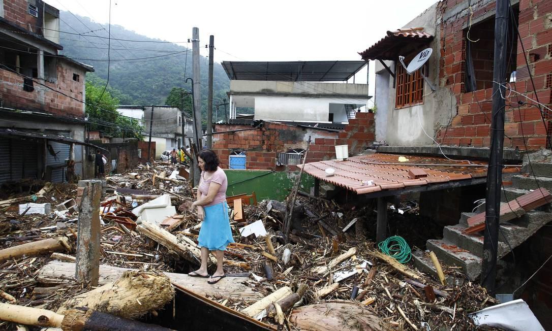 Desolada, moradora confere o cenário de destruição em torno de sua casa, em Xerém Foto: Pablo Jacob / Agência O Globo