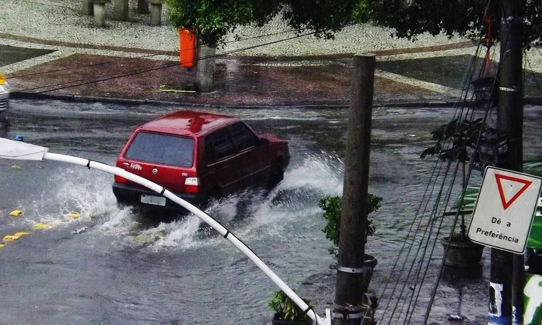 Carro enfrenta a enxurrada na Praça do Valqueire, na Zona Oeste do Rio Foto: Foto da leitora Mariana Marques / Eu-repórter