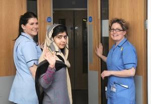 Malala acena na saída do hospital Queen Elizabeth, onde estava internada Foto: AP/Queen Elizabeth Hospital