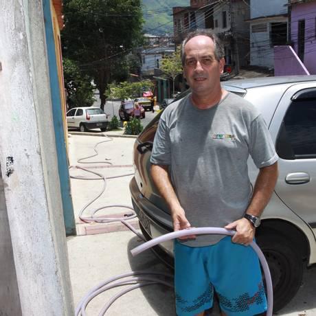 Improviso. Ivan Rodrigues usa uma mangueira para pegar água de um vizinho Foto: / Pedro Teixeira