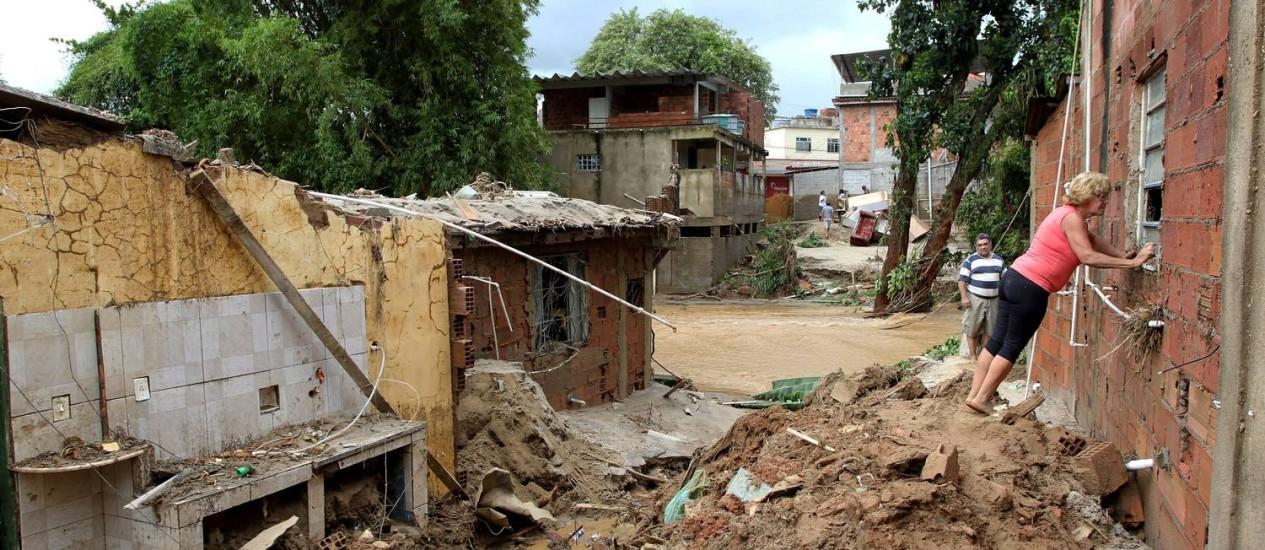 Moradora observa estragos em moradias em Xerém, em Duque de Caxias Foto: Domingos Peixoto / O Globo