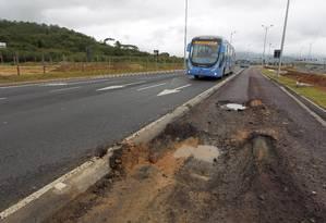 Ônibus do BRT TransOeste passa fora da via exclusiva devido a buracos na pista em Guaratiba Foto: Custodio Coimbra / O Globo