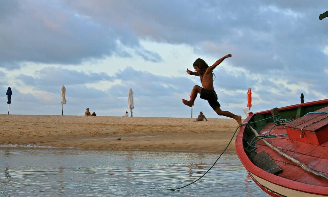 Maré baixa. Barco ancorado na Praia Central serve de trampolim para o menino Foto: Jason Butterfield/Especial para O Globo