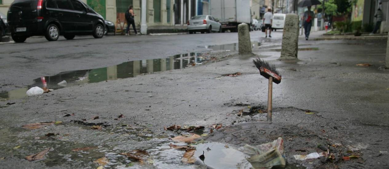 Descaso. Calçada esburacada, asfalto em péssima condição e bueiro entupido na Rua Aristides Lobo Foto: Pedro Teixeira