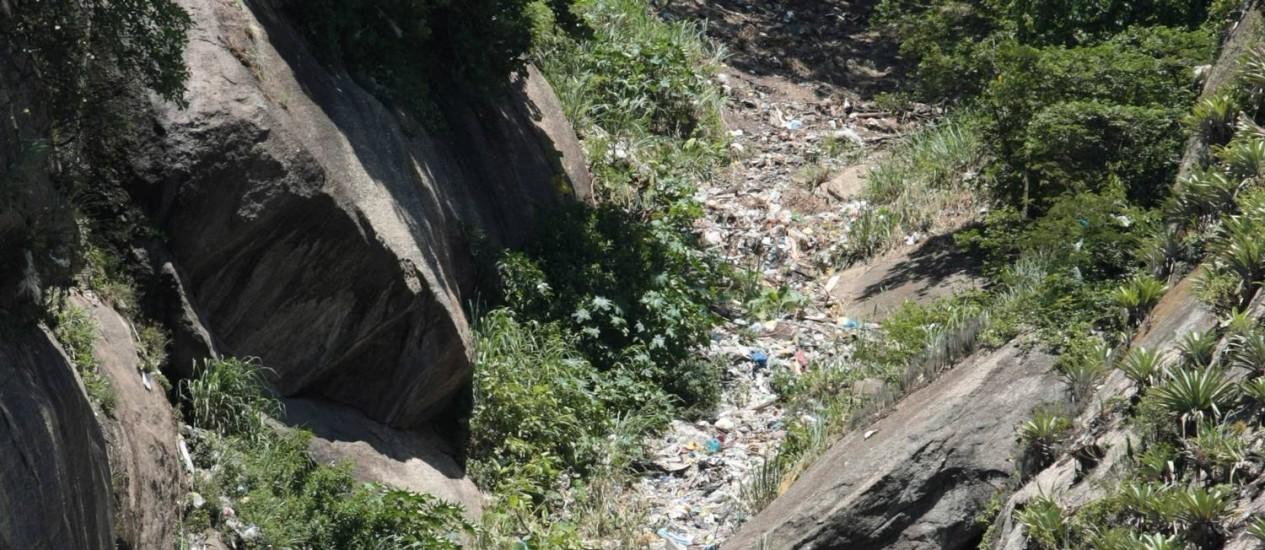 Morro abaixo. O lixo jogado do alto do morro desce pela encosta Foto: Foto: Hudson Pontes