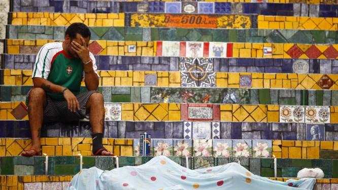 Amigo de Selarón, o argentino Cesar Gomez, chora ao lado do corpo do artista nas escadarias da Lapa Foto: Pablo Jacob / O Globo