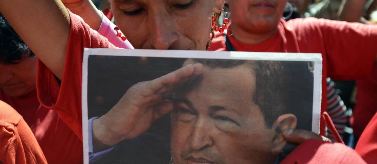 Partidária de Chávez carrega cartaz com foto do presidente em manifestação de posse simbólica Foto: AFP/LEO RAMIREZ