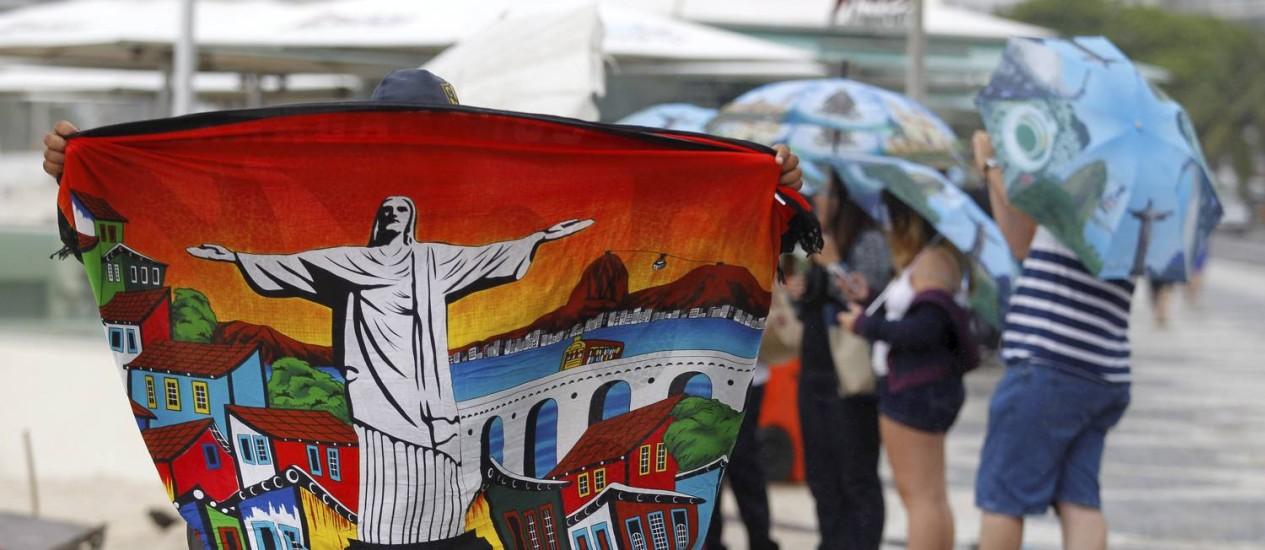 Com guarda-chuvas com cenários do Rio, turistas passeiam na Orla de Copacabana Foto: Custódio Coimbra / O Globo