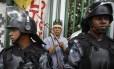 Munido de um arco e flecha, um indígena guarda a entrada do antigo Museu do Índio, no Maracanã. Policiais do Batalhão de Choque da Polícia Militar cercam o prédio, cuja reapropriação está prevista para este sábado