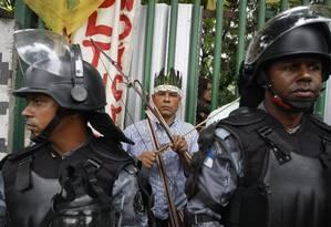Munido de um arco e flecha, um indígena guarda a entrada do antigo Museu do Índio, no Maracanã. Policiais do Batalhão de Choque da Polícia Militar cercam o prédio, cuja reapropriação está prevista para este sábado Foto: EDUARDO NADDAR / O GLOBO