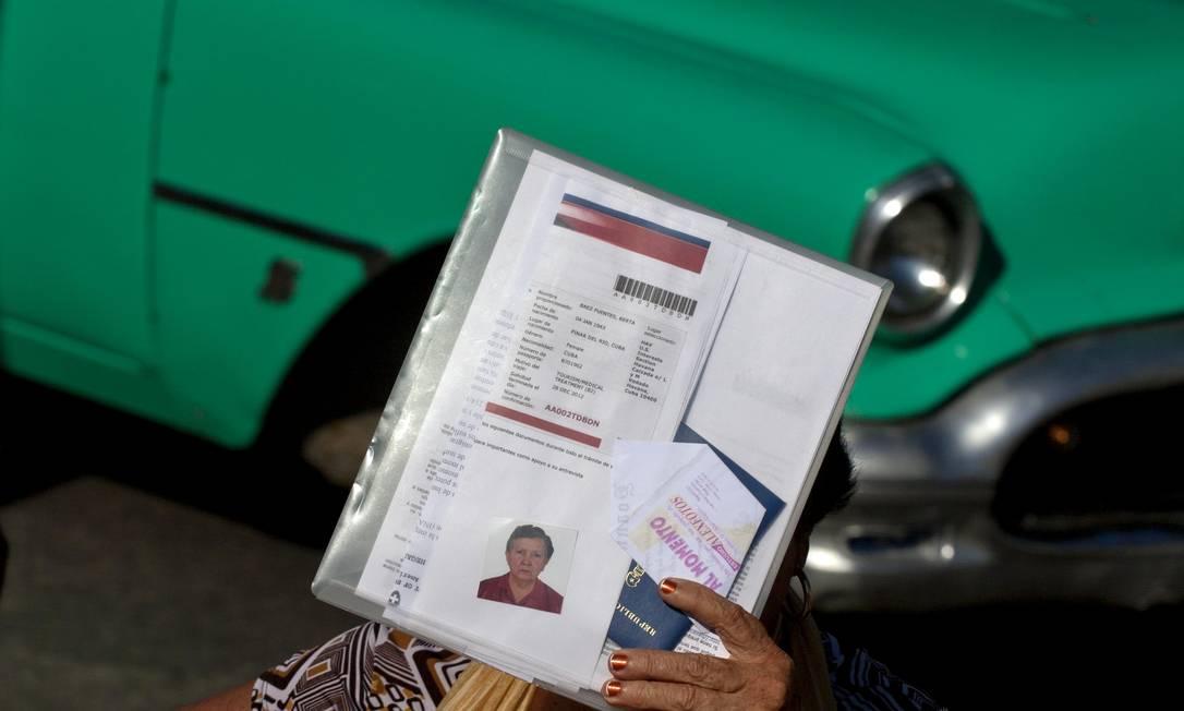Mulher se protege do sol com seus documentos enquanto espera do lado de fora da Seção de Interesses dos EUA em Havana Foto: AP/14-1-2013
