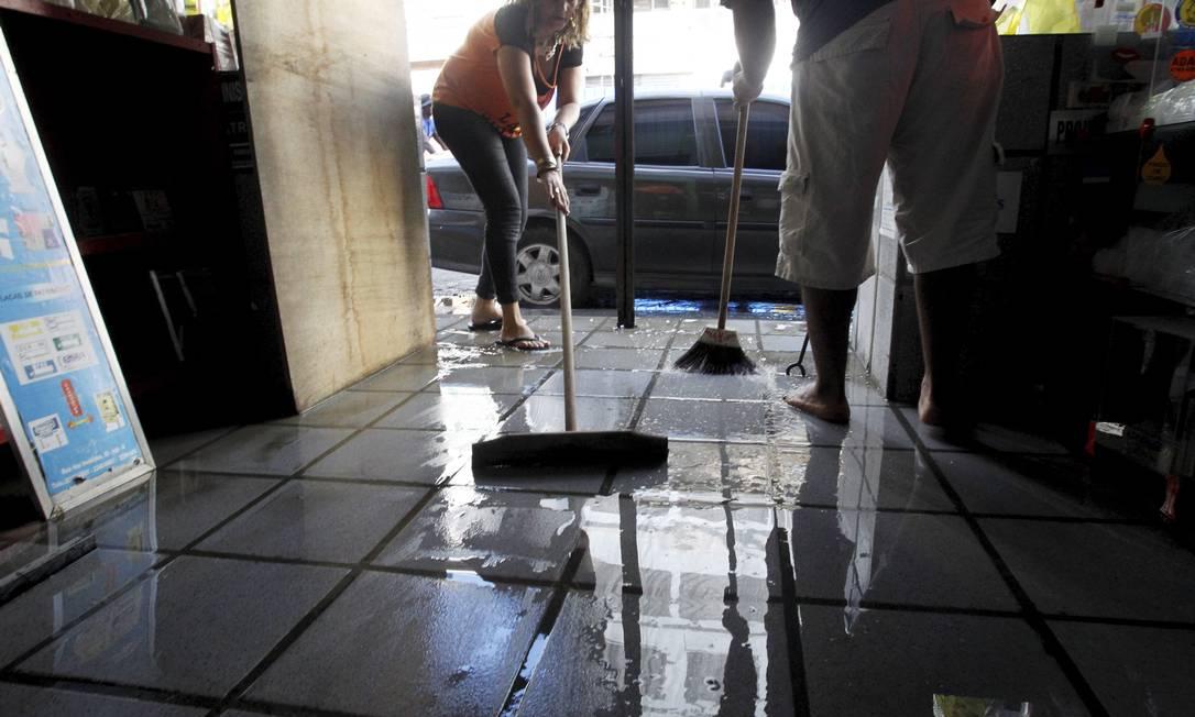 Comerciantes limpam estabelecimento no Centro do Rio Custódio Coimbra / Agência O Globo