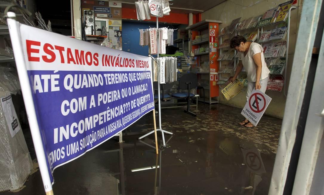 Na Rua dos Inválidos, cartaz mostra a indignação de comerciantes da região que tiveram lojas invadidas pela lama Custódio Coimbra / Agência O Globo