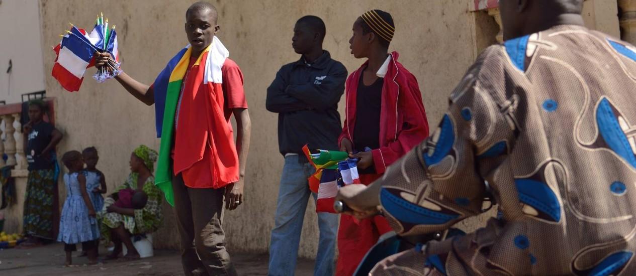 Malinês vende bandeira da França em uma rua de Bamako Foto: ERIC FEFERBERG / AFP