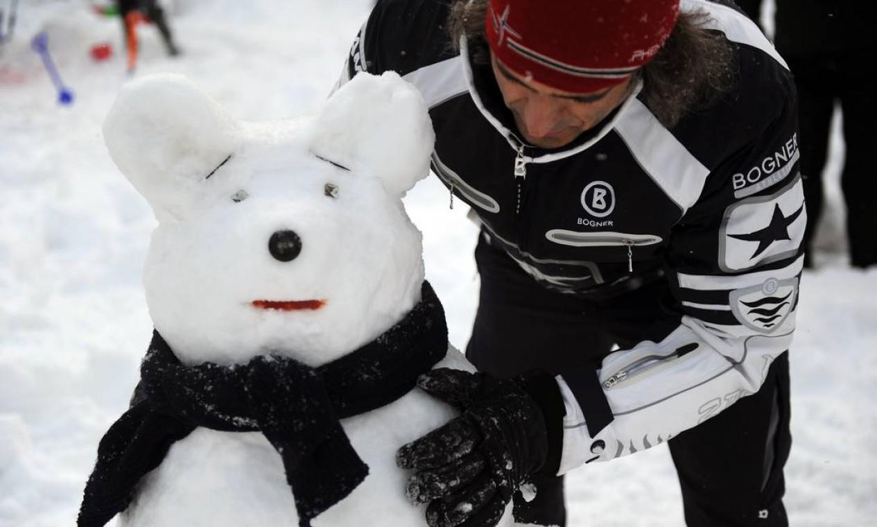 Um homem constrói um boneco de neve em Moscou em um parque de Moscou Foto: ANDREY SMIRNOV / AFP