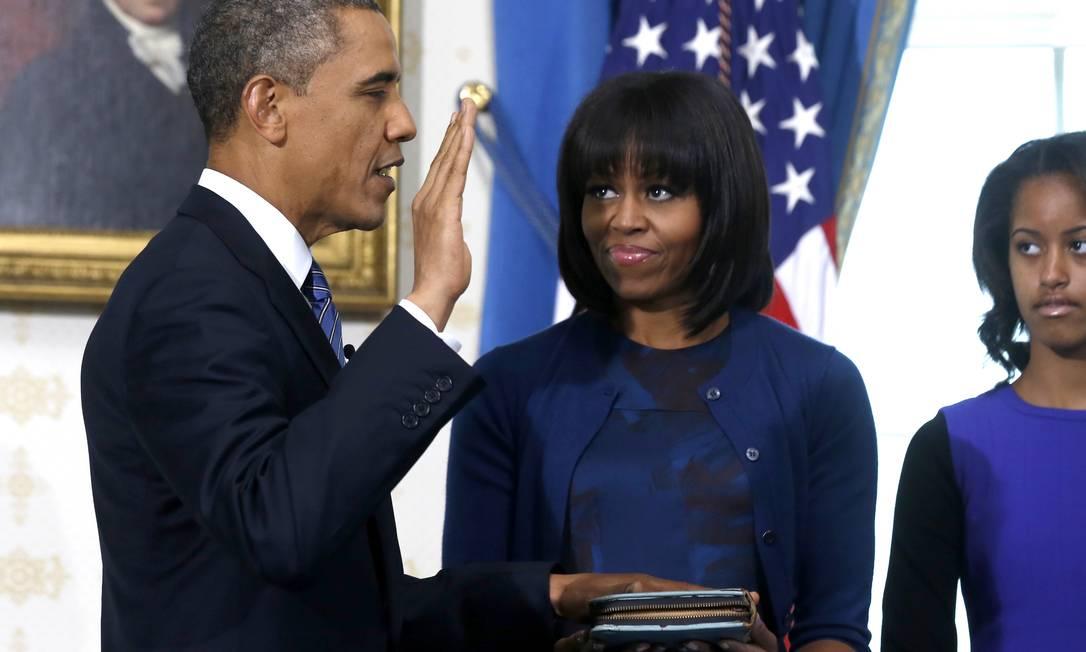 O presidente dos EUA, Barack Obama, faz seu juramento de posse na Casa Branca, ao lada da esposa, Michelle, e sua filha, Malia LARRY DOWNING / AP