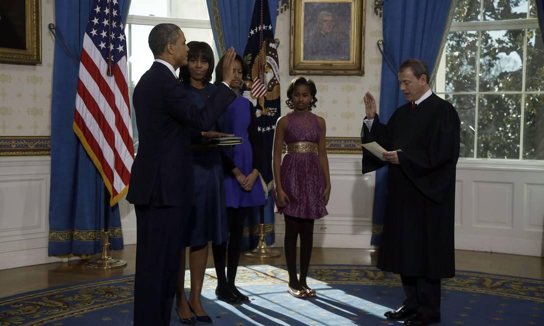 Obama colocou a mão sobre a Bíblia e recitou o juramento de 25 palavras que foi lido para ele pelo presidente da Suprema Corte dos Estados Unidos, John Roberts CHARLES DHARAPAK / AFP