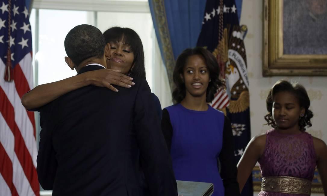 """Depois do juramento, o presidente abraçou a esposa Michelle e disse """"obrigado"""", depois que ela o parabenizou pela posse CHARLES DHARAPAK / AFP"""