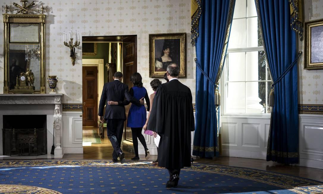 Poucos minutos depois, o presidente e a família deixam o Salão Azul da Casa Branca. Obama e seu vice, Joe Biden, irão tomar posse oficialmente na segunda-feira, em uma esperada cerimônia pública no Capitólio, que abriga o Congresso americano Brendan Smialowski / AP