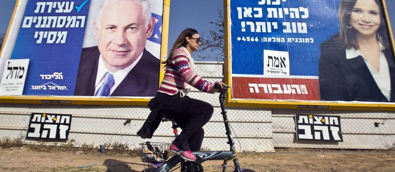 Israelense passa por cartaz do primeiro-ministro, Benjamin Netanyahu, e de Shelly Yachimovich Foto: JACK GUEZ / AFP