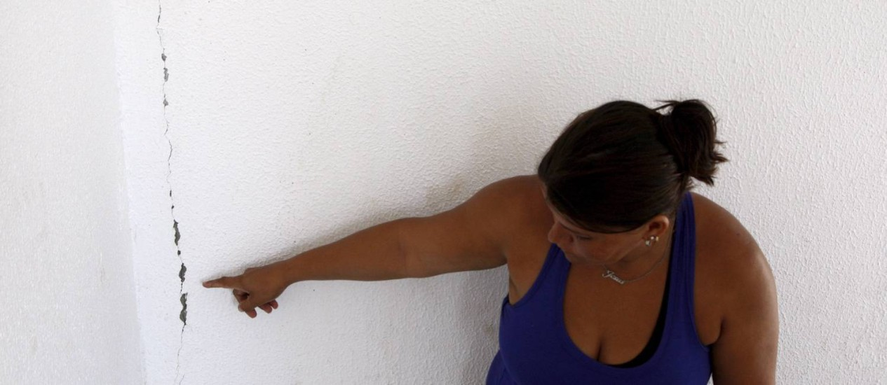 """Má qualidade. Simone mostra a rachadura existente num prédio do Bairro Carioca: """"A prefeitura correu para entregar as obras porque era período eleitoral"""" Foto: Marcos Tristão / O Globo"""