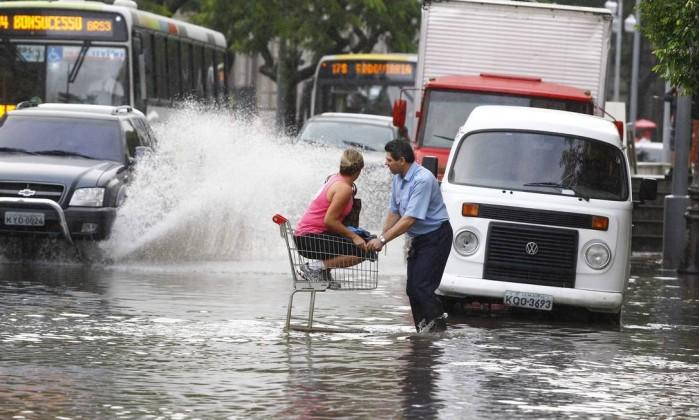 Para fugir do alagamento, mulher é carregada em um carrinho de compras na Rua do Catete Pablo Jacob / O Globo