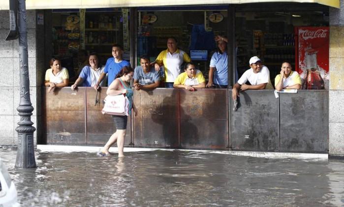 Mulher passa pela enorme poça d'água que se formou na Rua do Catete Pablo Jacob / O Globo