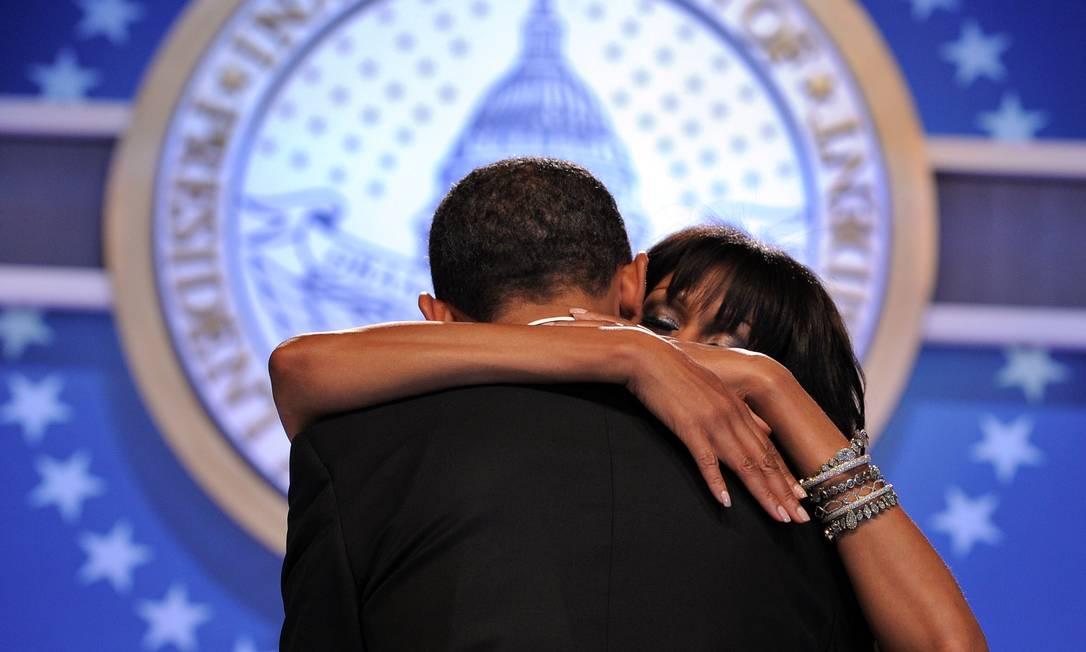 Michele abraça Obama durante a música JEWEL SAMAD / AFP