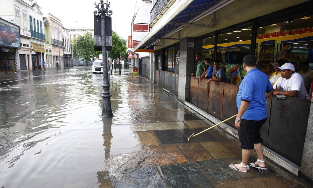 Comerciante tenta empurrar a água da calçada na Rua do Catete Pablo Jacob / O Globo