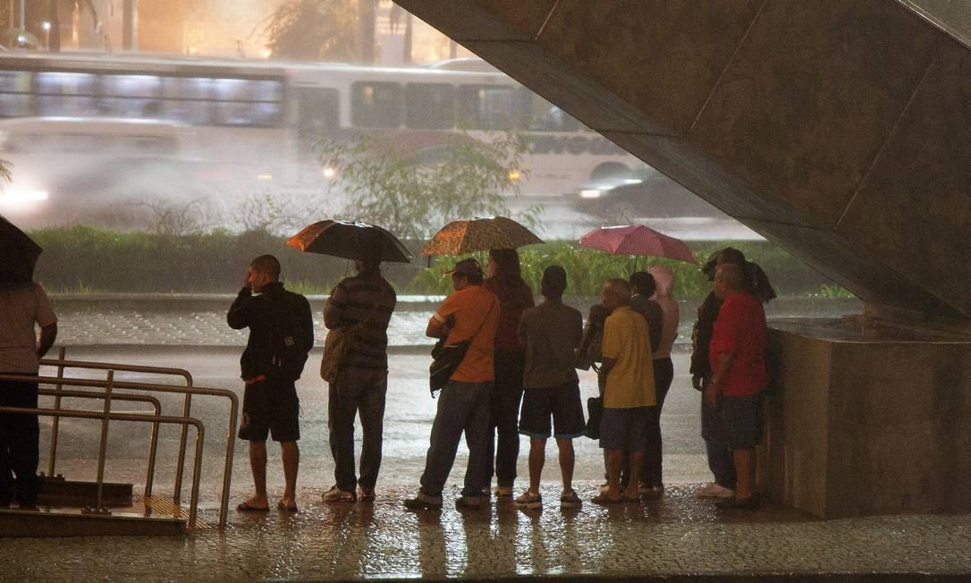 Pedestres se encondem da chuva na Avenida Presidente Vargas, na manhã desta terça-feira Fernando Quevedo / O Globo