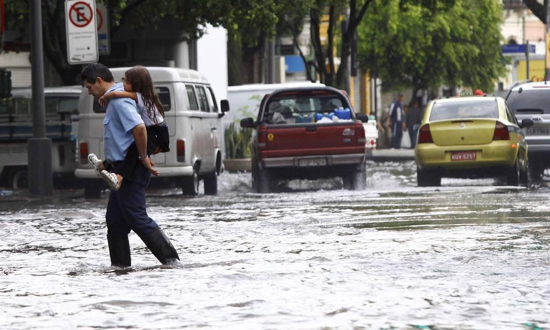 Homem e criança atravessam a Rua do Catete alagada Pablo Jacob / O Globo