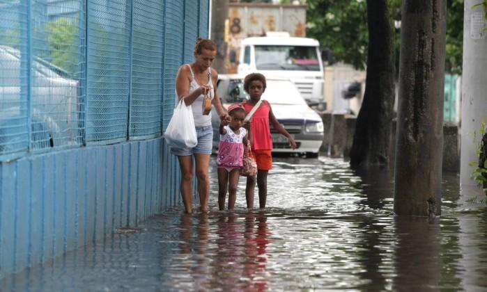 Mulher e crianças passam dentro d'água na Rua Viúva Cláudia, nas proximidades do Jacaré Bruno Gonzalez / O Globo