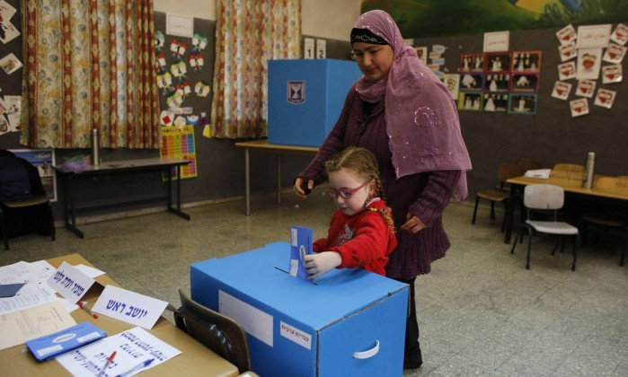 Uma menina deposita o voto de sua mãe em uma seção eleitoral na cidade de Sakhnin AMMAR AWAD / REUTERS