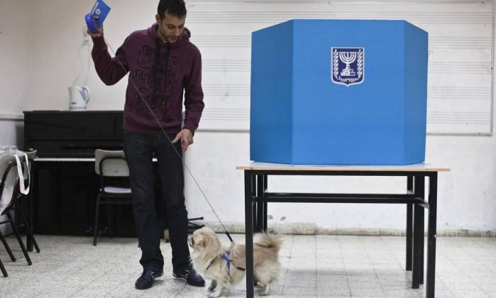 Um homem leva seu cachorro para uma seção eleitoral Tel Aviv NIR ELIAS / REUTERS